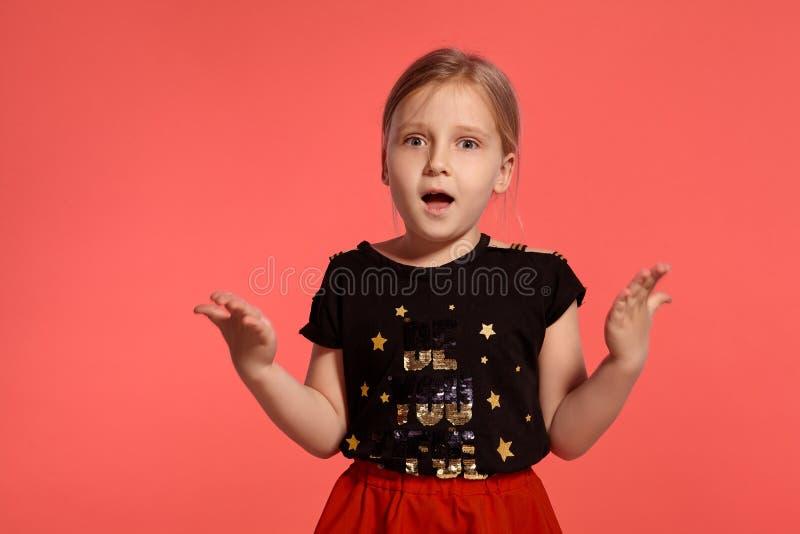 Close-up disparado de uma senhora pequena loura encantador em um vestido combinado que levanta contra um fundo cor-de-rosa fotografia de stock