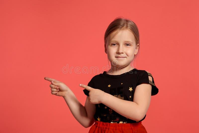 Close-up disparado de uma senhora pequena loura encantador em um vestido combinado que levanta contra um fundo cor-de-rosa imagem de stock royalty free