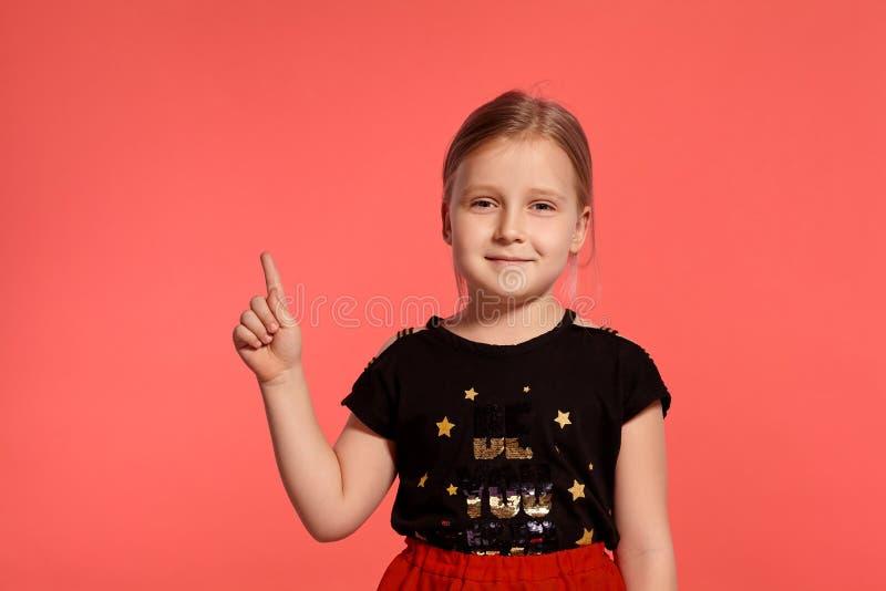 Close-up disparado de uma senhora pequena loura encantador em um vestido combinado que levanta contra um fundo cor-de-rosa imagem de stock