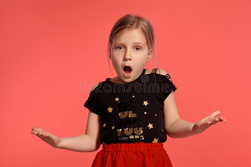 Close-up disparado de uma senhora pequena loura encantador em um vestido combinado que levanta contra um fundo cor-de-rosa imagens de stock royalty free