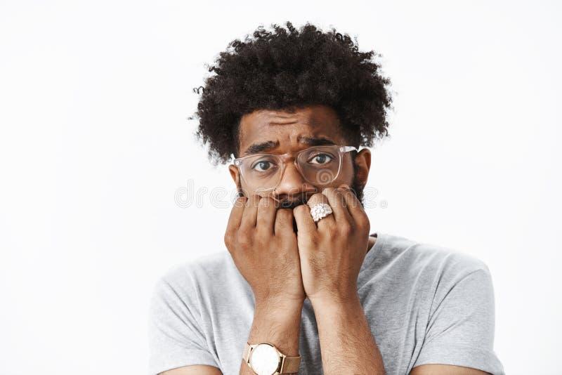 Close-up disparado do homem afro-americano novo assustado e incerto com penteado afro na mordedura do rel?gio e dos vidros fotografia de stock royalty free