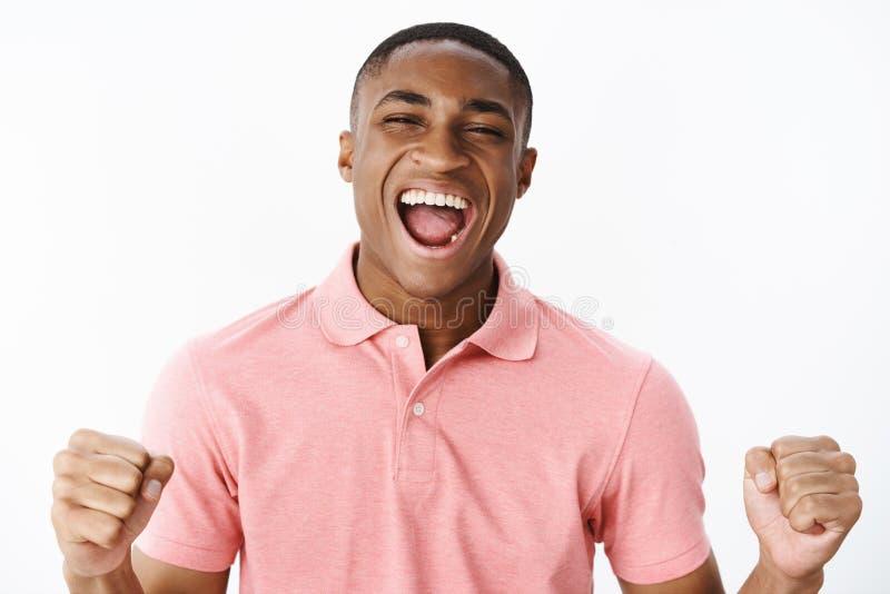 Close-up disparado dos punhos de aperto afro-americanos felizes novos sobre-emotivos e entusiasmados carismáticos do homem na ale imagens de stock