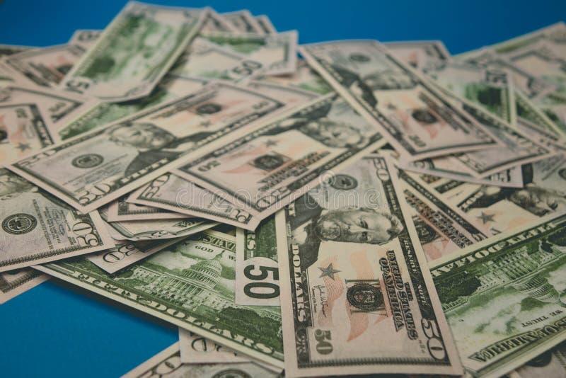 Close-up dispersado das notas de d?lar cinq??nta d?lares de fundo azul fotografia de stock royalty free
