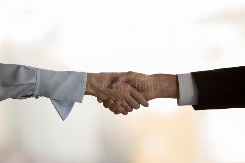 Close up of diverse business partners handshake at briefing. Close up of diverse business partners shake hand closing deal after successful negotiations stock images