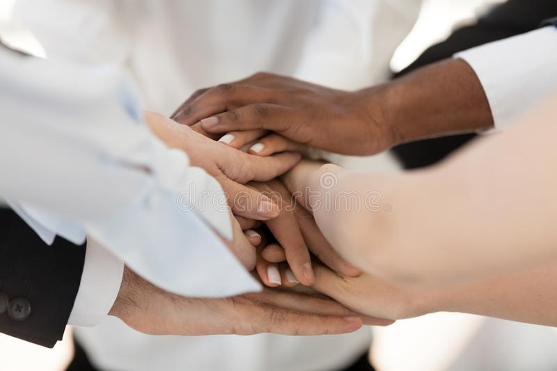 Close up diverse people stack their hands together stock photography