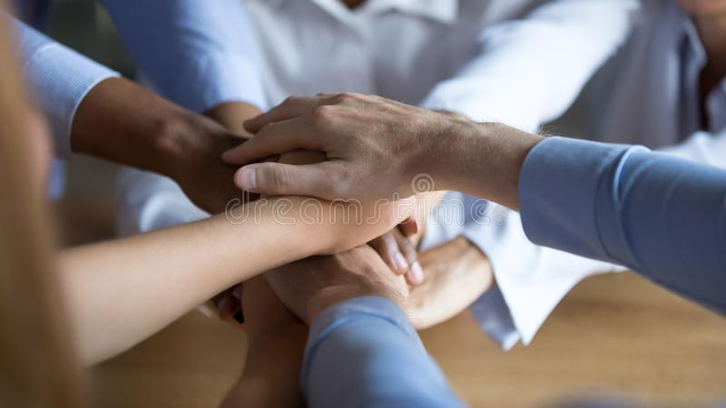 Close up diverse business people putting hands together, showing support stock photo