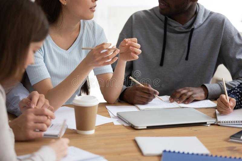 Close up of diverse students study together making notes stock images