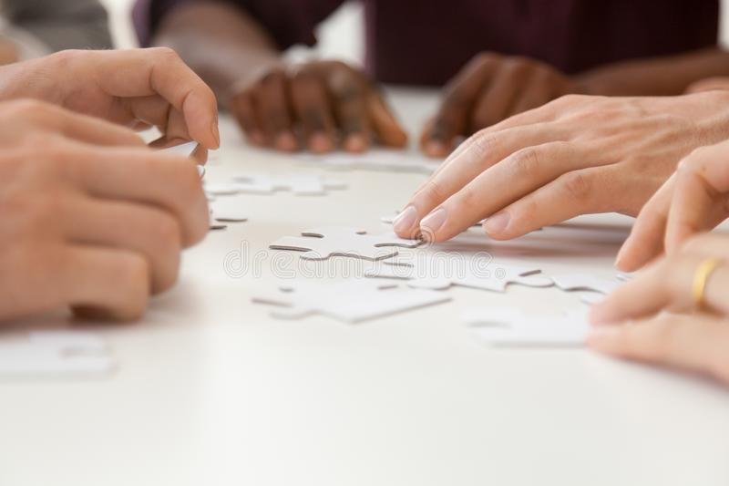 Close up of diverse work team assembling puzzle together royalty free stock image