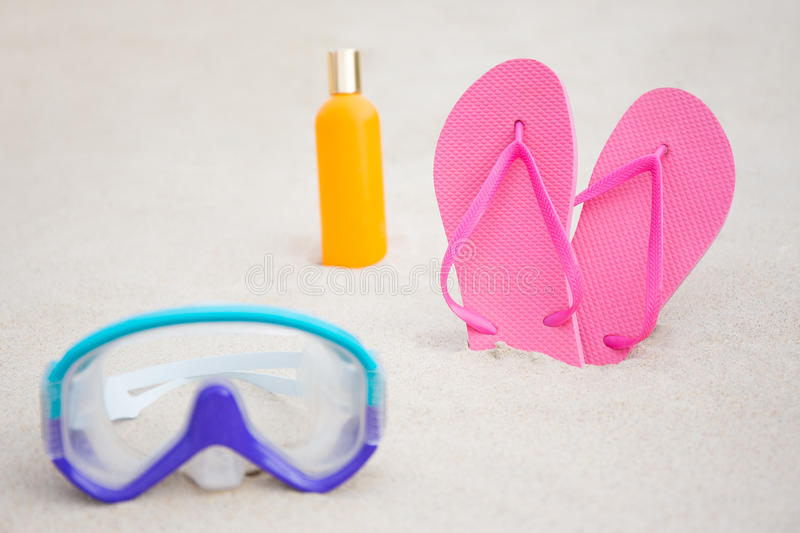 Close up of diving mask, flip flops and suntan lotion bottle on. Close up of diving mask, pink flip flops and suntan lotion bottle on sandy beach royalty free stock images