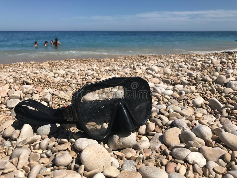 Close-up of a diving mask on the stones of a beach stock photo