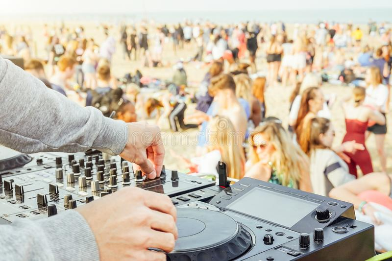 Close up of DJ`s hand playing music at turntable at beach party festival - Crowd people dancing and having fun in club outdoor - stock photos