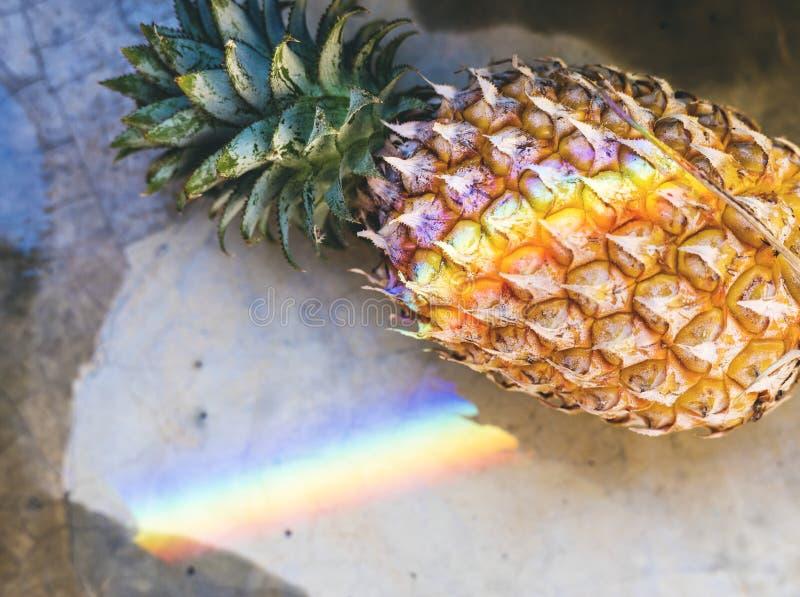 Close up do abacaxi fresco com luz de prisma do arco-íris imagem de stock