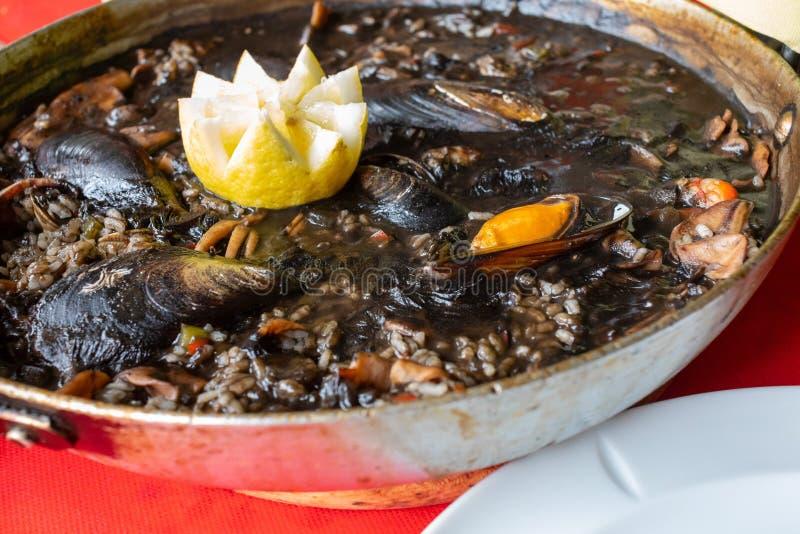 Close-up do arroz preto com calamar – em mexilhões da tinta, em moluscos e no outro marisco foto de stock