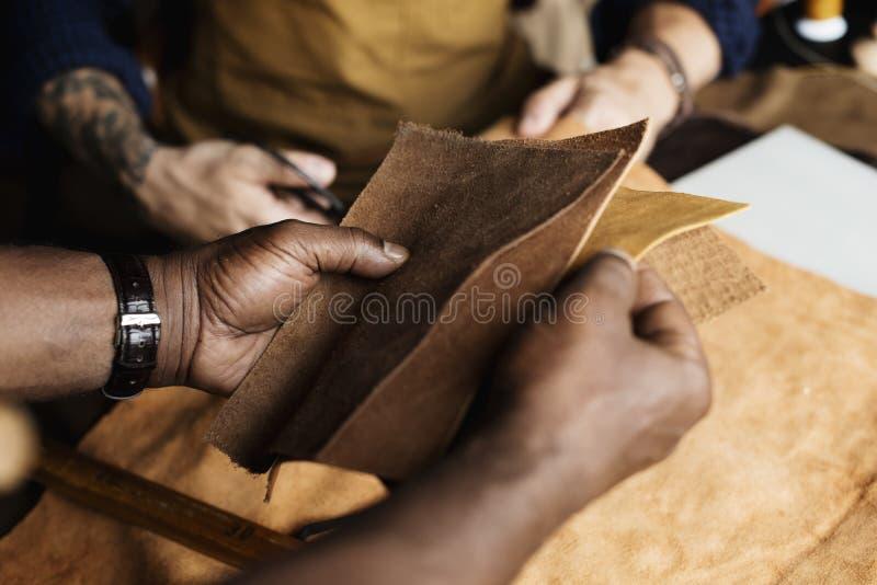 Close up do artesão que guarda o artesanato de couro foto de stock