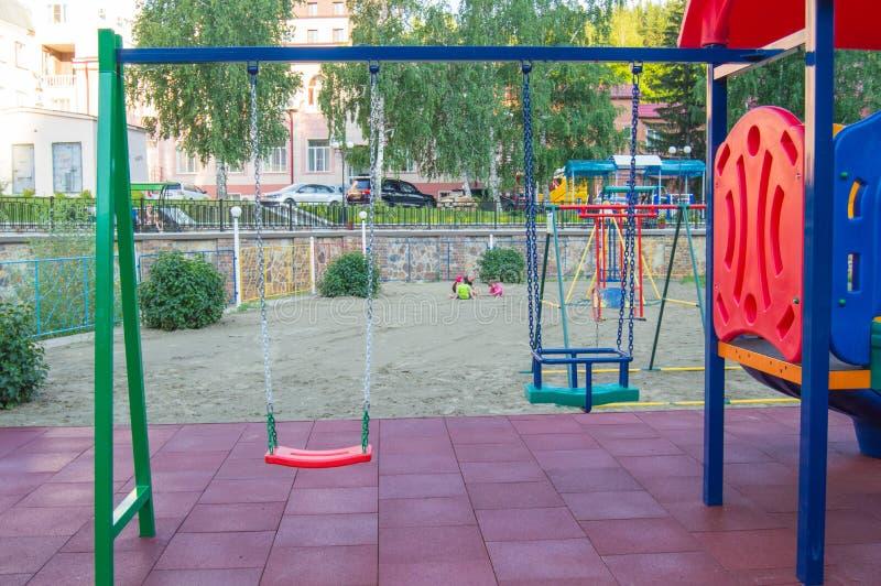 Close-up do balanço plástico colorido vazio do bebê no campo de jogos no parque no dia de verão imagens de stock