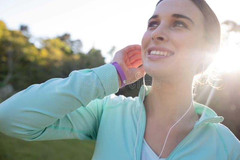 Close-up do basculador fêmea de sorriso com os fones de ouvido que tomam uma ruptura do exercício foto de stock royalty free