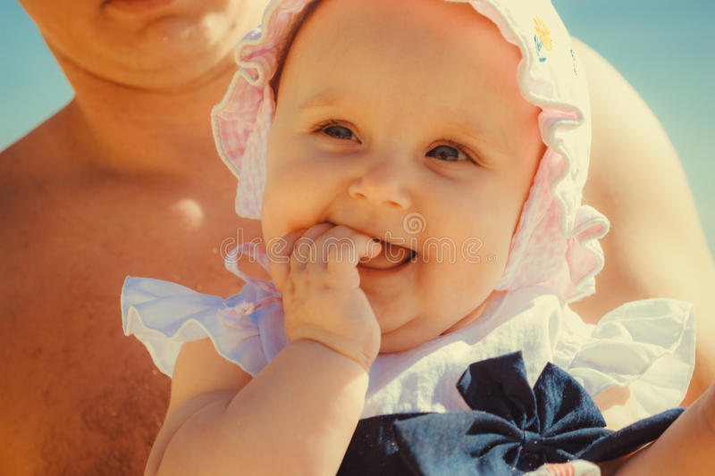 Close up do bebê pequeno feliz nas mãos do pai imagem de stock