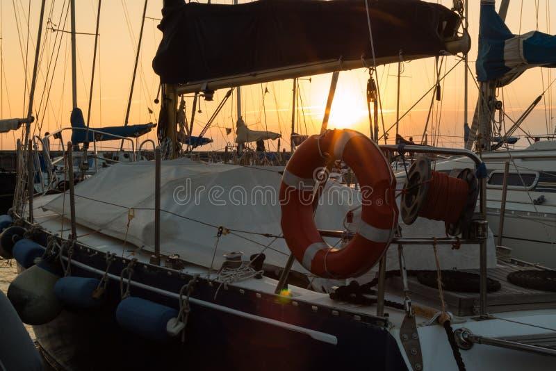 Close up do boia salva-vidas alaranjado e da corda rolada no barco de navigação imagem de stock