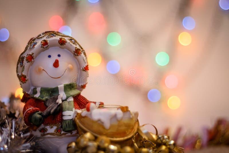 Close-up do boneco de neve no fundo do ouropel colorido obscuro das luzes e do ano novo feliz imagem de stock