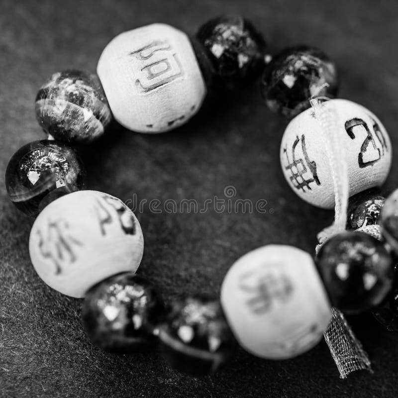 Close-up do bracelete do grânulo em preto e branco com símbolos asiáticos fotografia de stock