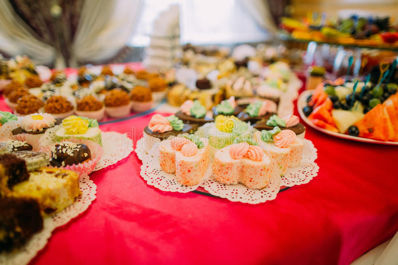 Close-up do bufete servido fantasia da sobremesa na toalha de mesa vermelha no ajuste luxuoso do restaurante do partido fotos de stock royalty free