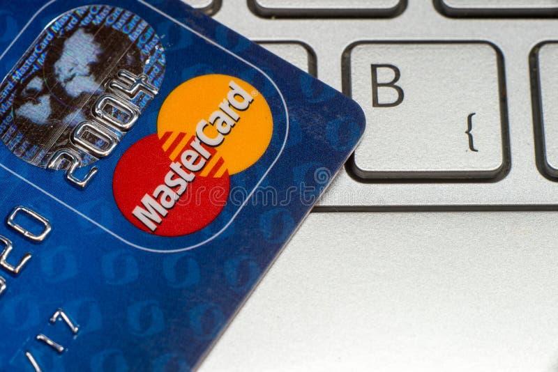 Close up do cartão de crédito MasterCard No teclado do portátil imagem de stock