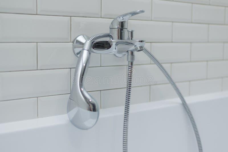 Close-up do chuveiro do cromo, torneira, nos azulejos decorativos cobertos banheiro com os tijolos lustrosos brancos foto de stock royalty free