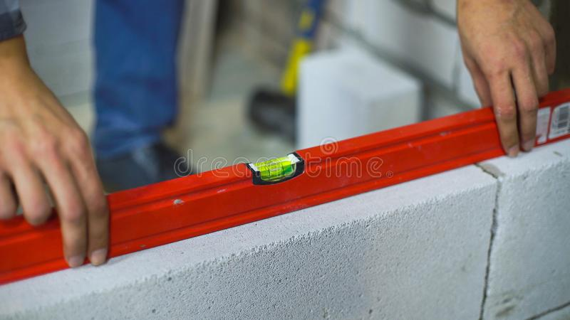 Close up do construtor que verifica a regularidade do muro de cimento ventilado com o nível de bolha imagens de stock