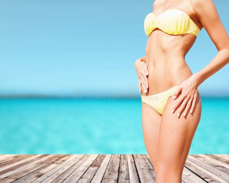 Close up do corpo fêmea no biquini na praia foto de stock