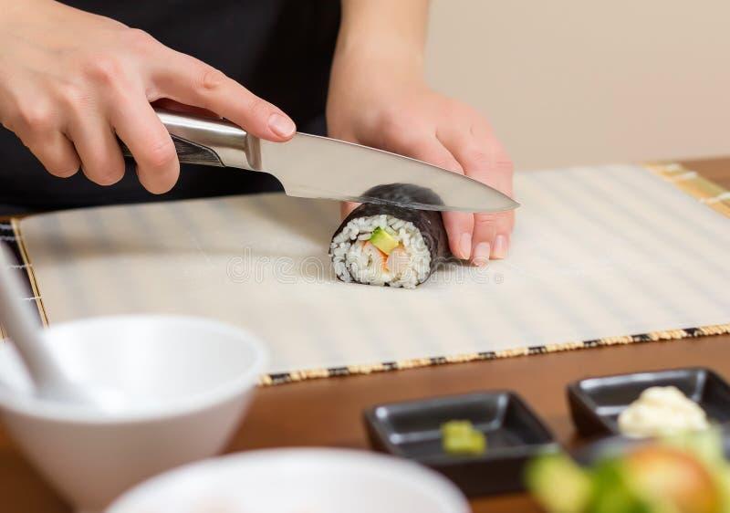 Close up do cozinheiro chefe da mulher que corta o rolo de sushi japonês foto de stock