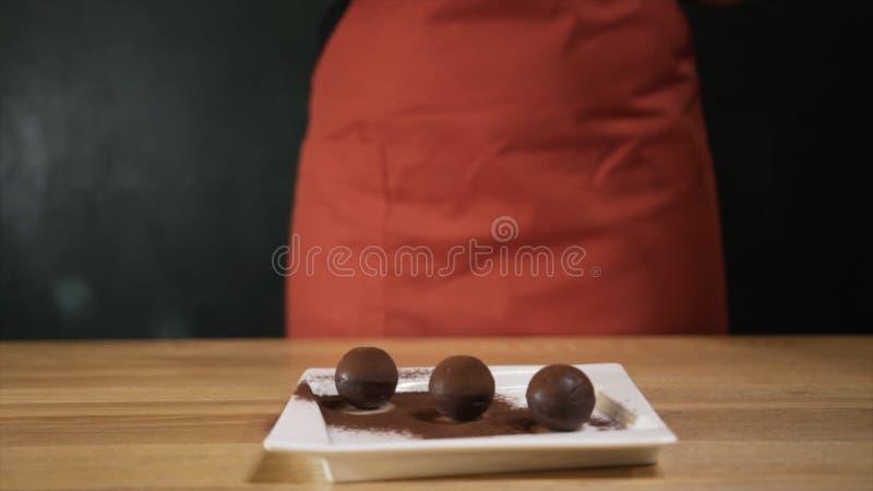 Close-up do cozinheiro chefe f?mea que faz a sobremesa do chocolate e que polvilha a com o chocolate raspado a??o Chocolate sabor fotos de stock