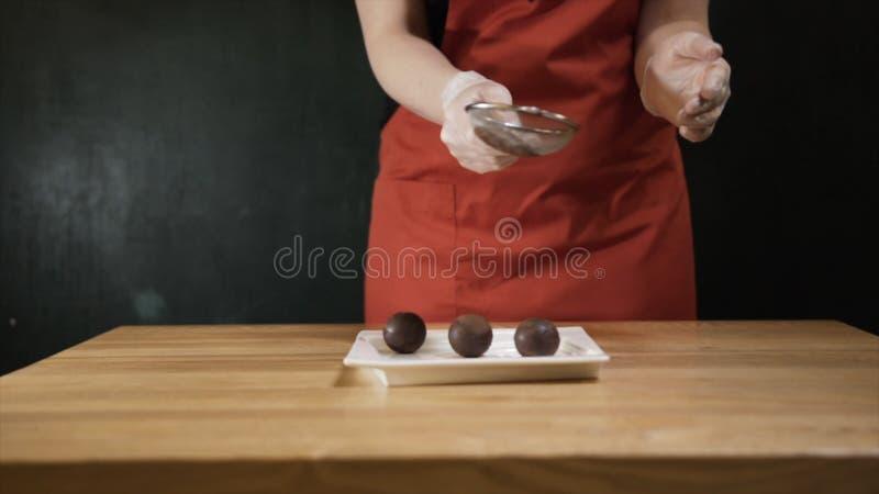 Close-up do cozinheiro chefe f?mea que faz a sobremesa do chocolate e que polvilha a com o chocolate raspado a??o Chocolate sabor foto de stock royalty free