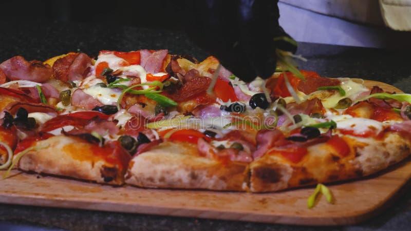 Close-up do cozinheiro chefe que prepara a pizza italiana Quadro O cozinheiro chefe profissional decora verdes com pizza italiana imagem de stock royalty free