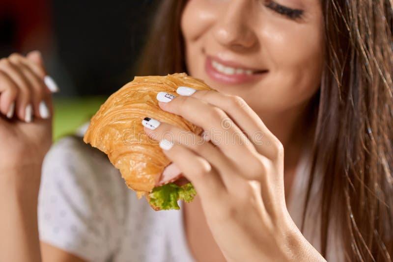 Close up do croissant saboroso nas mãos da menina bonita fotografia de stock royalty free