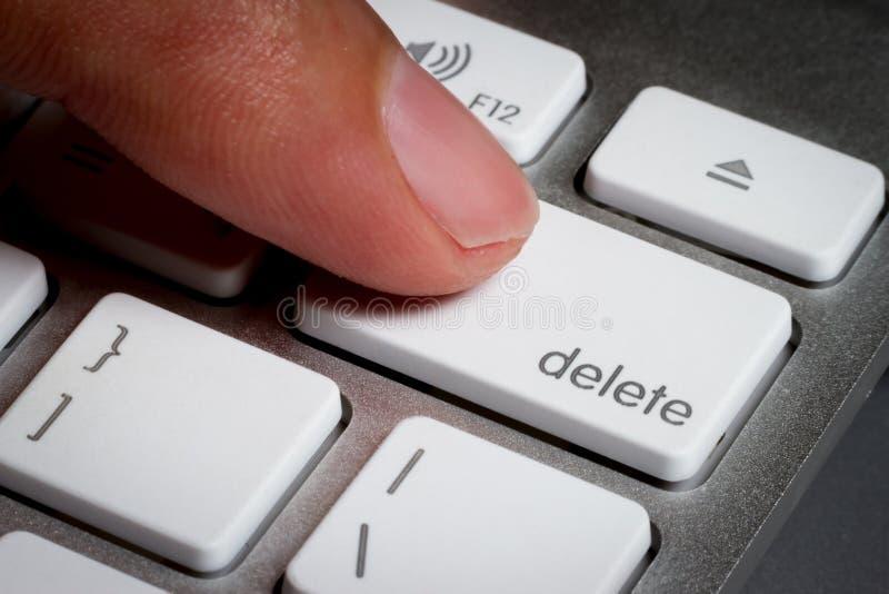 Close up do dedo na chave de supressão em um teclado foto de stock
