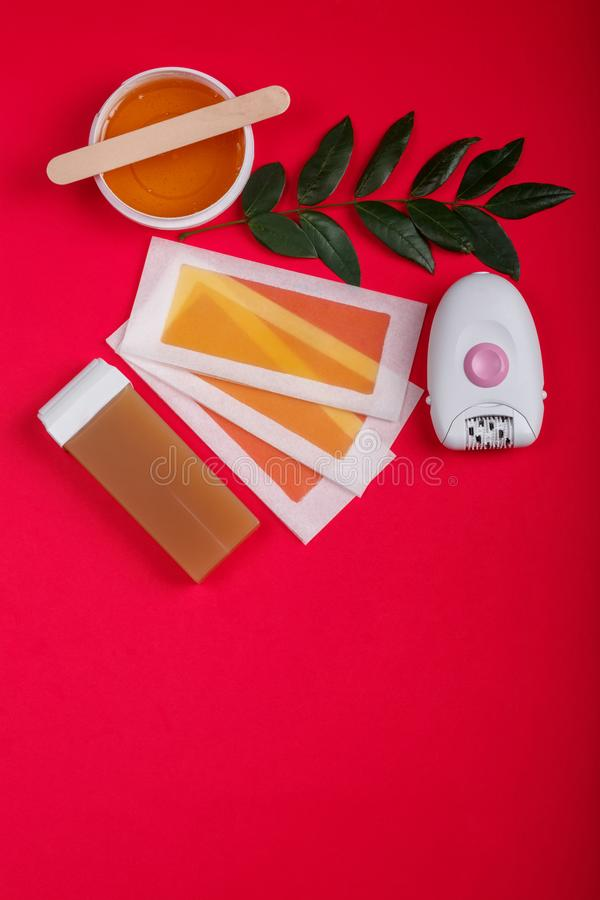 Close-up do epilator, cera, tiras da cera, em um fundo vermelho fotos de stock