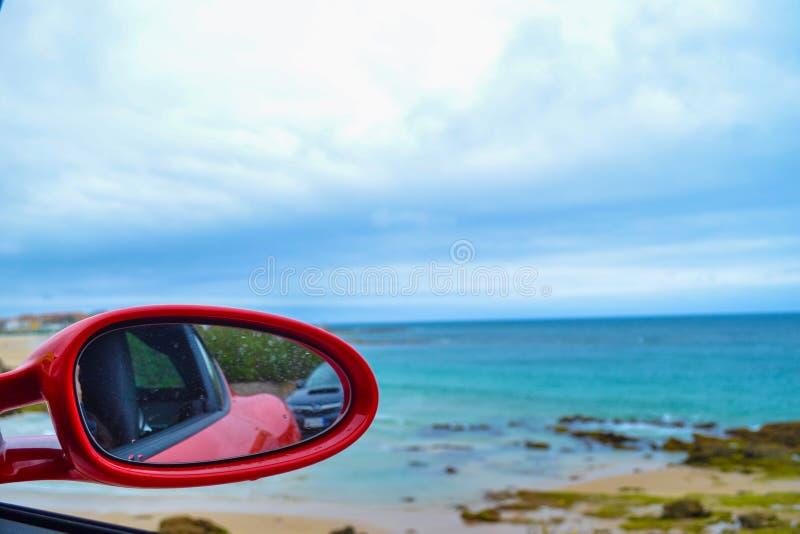 Close up do espelho de rearview de um carro vermelho com a praia defocused em imagem de stock