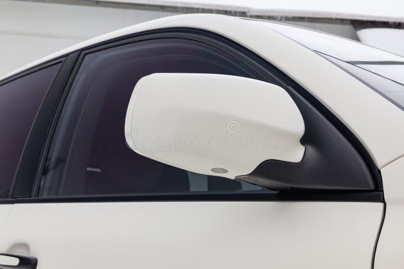 Close-up do espelho esquerdo lateral com repetidor da pisca-pisca e janela do corpo de carro SUV branco na rua que estaciona em s imagem de stock royalty free