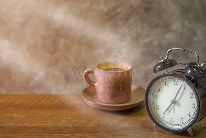 Close-up do estilo retro do vintage do pulso de disparo do preto do alarme com o rosa de cor pastel do café do copo velho na tabe imagens de stock royalty free
