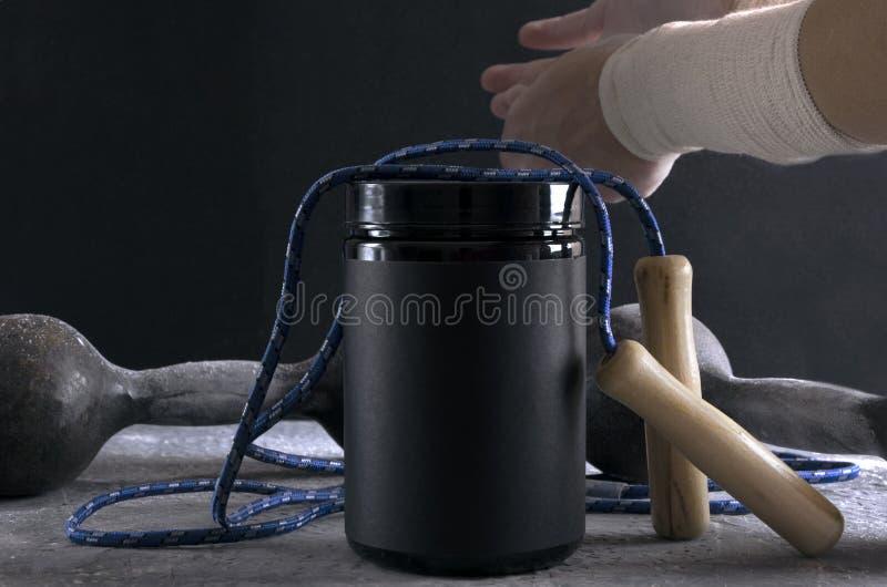 Close up do frasco da nutrição do esporte e do equipamento de esporte Desportista com as ataduras elásticas do apoio que preparam imagens de stock