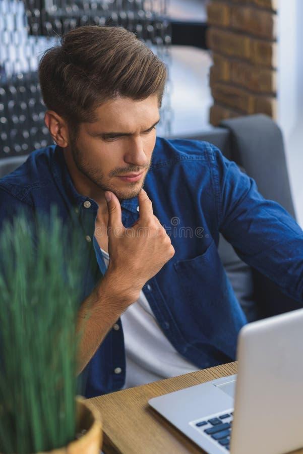 Close up do freelancer novo que pensa ao olhar o portátil imagens de stock
