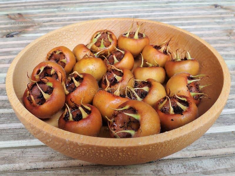 Close-up do fruto do germanica comum do Mespilus da nêspera em uma bacia de madeira imagem de stock royalty free