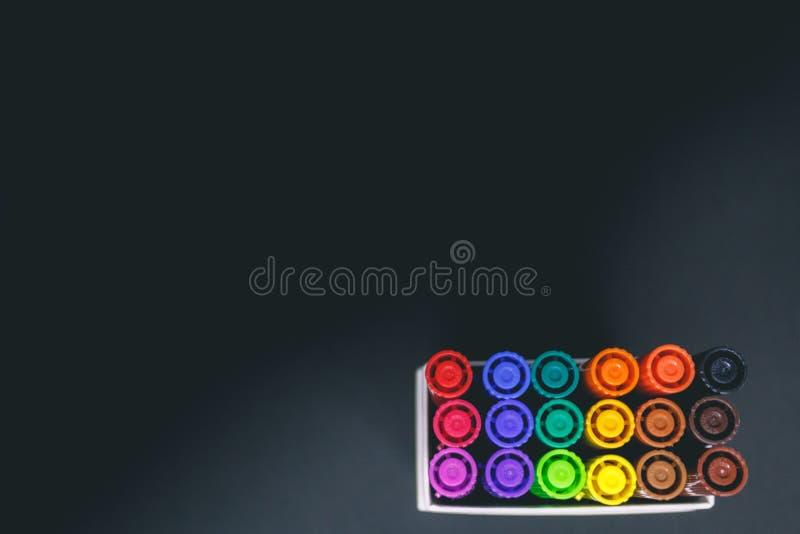 Close up do fundo preto colorido dos againts dos marcadores imagens de stock