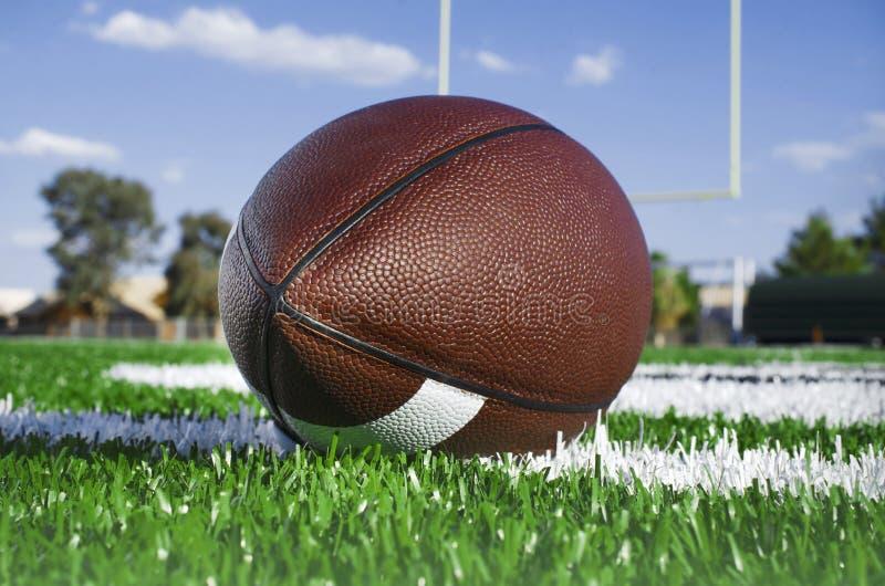 Close up do futebol americano no campo com cargo do objetivo fotos de stock royalty free