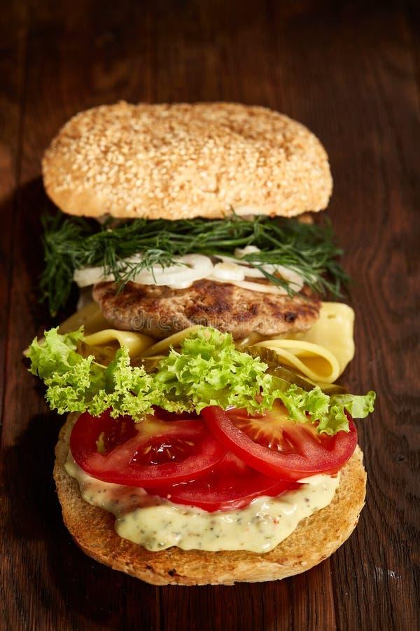Close-up do hamburguer americano tradicional com alface, queijo, cebola e tomate no fundo de madeira, vertical imagens de stock royalty free