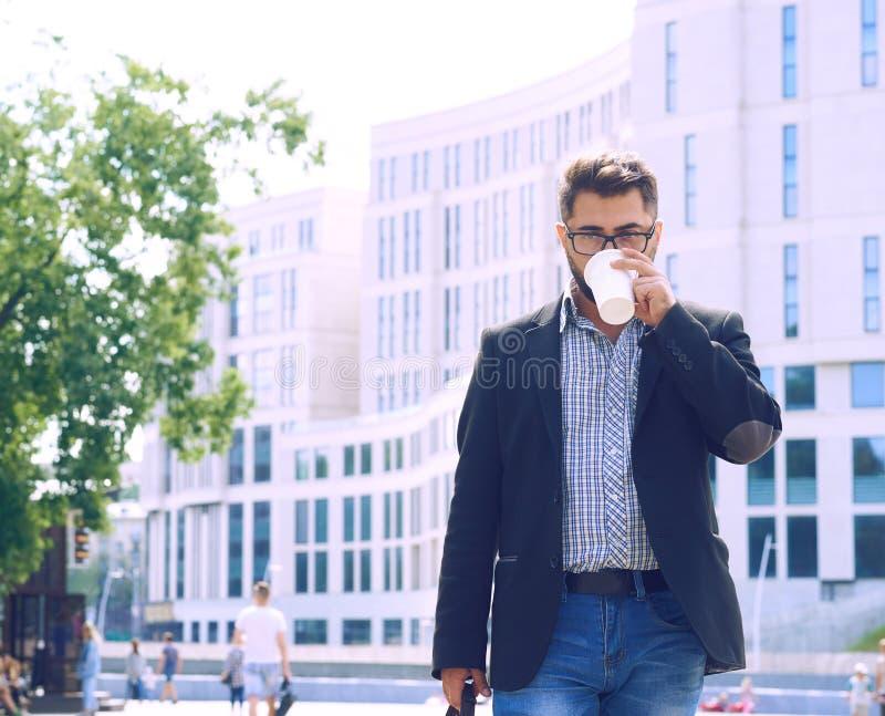 Close-up do homem beared novo nos vidros e do terno que guarda o café para levar embora e encaixotar no parque ensolarado, luz so foto de stock royalty free