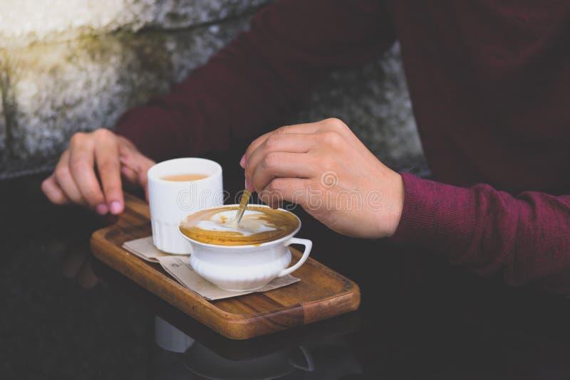 Close up do homem de Ásia da mão esquerda na camisa vermelha que agita o açúcar no copo branco pequeno do café quente fotografia de stock