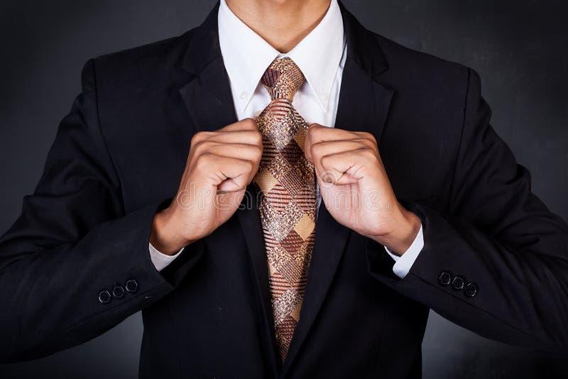Close up do homem de negócio que fixa seu laço do pescoço fotografia de stock royalty free