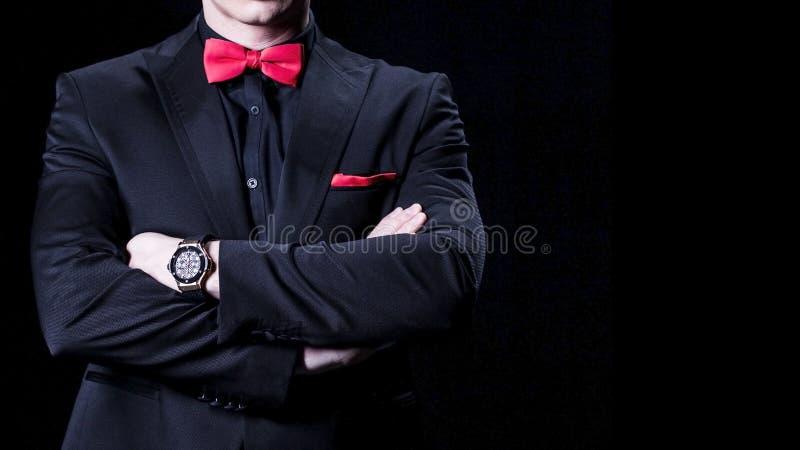 Close up do homem de negócios no terno luxuoso com braços cruzados Sobre o fundo preto Nenhuma cara imagens de stock royalty free