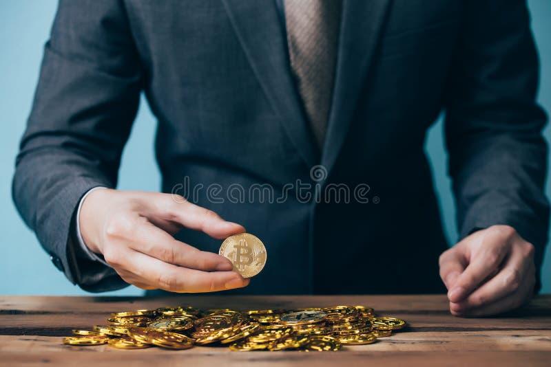 Close-up do homem de negócios que conta e que guarda o sinal das moedas - indicando do bitcoin a riqueza e o negócio de comércio  fotos de stock royalty free